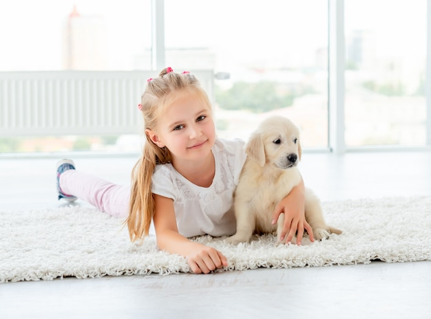Puppy of retriever and little girl