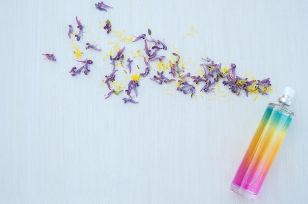 Puprle 꽃잎과 흰색 나무 바탕에 여러 가지 빛깔 된 향수 병 프리미엄 사진