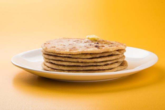 홀리제(holige)라고도 알려진 푸란 폴리(puran poli)는 홀리 축제 기간 동안 주로 소비되는 인도의 달콤한 플랫 브레드입니다. 다채로운 또는 나무 배경 위에 순수한 버터 기름이 든 접시에 제공됩니다. 선택적 초점