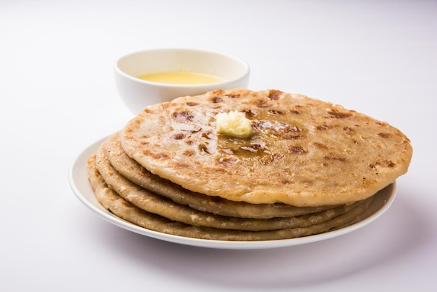 Puran poli, also known as holige, is an indian sweet flatbread consumed mostly during holi festival. served in a plate with pure ghee over colourful or wooden background. selective focus