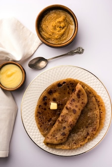Puran poli, also known as holige, is an indian sweet flatbread consumed mostly during holi festival. served in a plate with pure ghee over colourful or wooden background Premium Photo