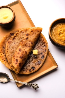 Puran poli, also known as holige, is an indian sweet flatbread consumed mostly during holi festival. served in a plate with pure ghee over colourful or wooden background