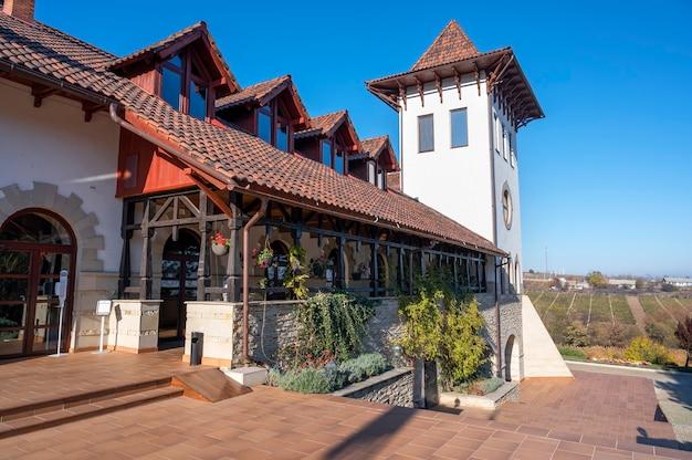 푸르 카리 와이너리 본관은 옛 스타일로 만들어졌습니다. 전경의 테라스, 입구 및 녹지. 몰도바의 좋은 날씨