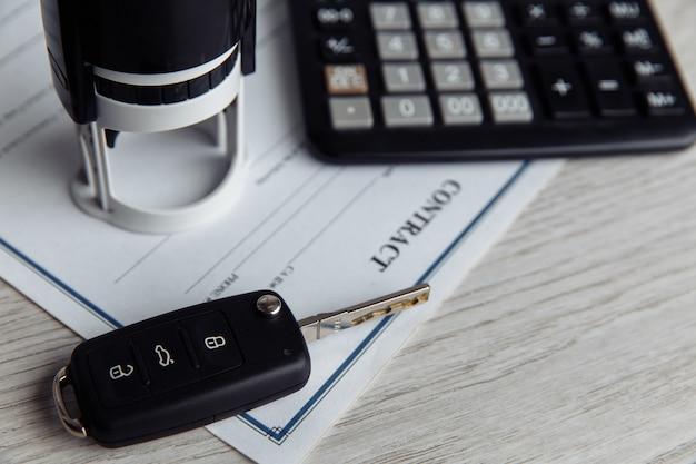 Договор купли-продажи автомобиля с контрактом, печатью, калькулятором и ключом крупным планом. концепт для продажи автомобиля