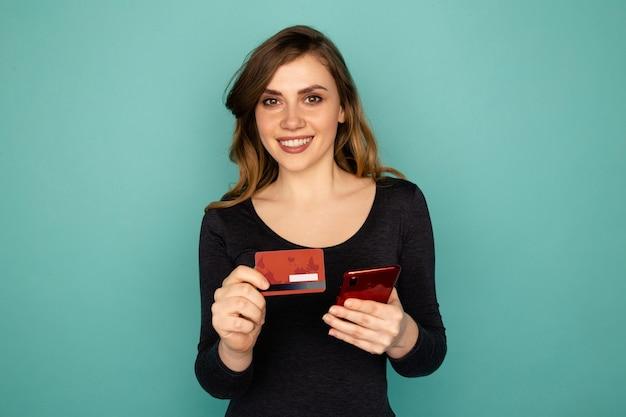 Купить онлайн-концепцию. девушка с мобильным телефоном и изолированной кредитной картой.