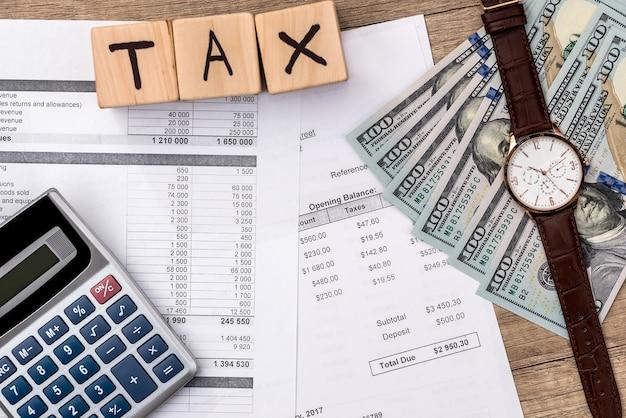 注文書、ドル、テキスト税付きの木製の立方体、ペン、電卓