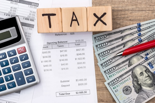 Purchase order, dollar, wooden cubes with text tax, pen and calculator