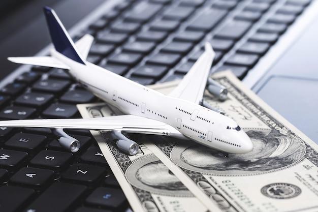 オンラインでチケットを購入します。ノートパソコンのキーボード上の小さなおもちゃの飛行機と米ドル紙幣