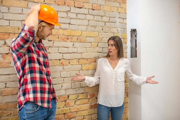 Purchaser talking to the construction worker and looking unpleased