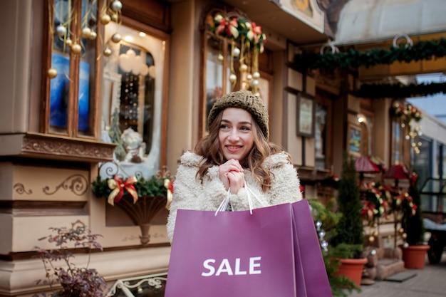 Покупка товаров и подарков. покупки для семьи. рождественские продажи концепции. женщина, держащая подарок хозяйственной сумки xmas. большая скидка.
