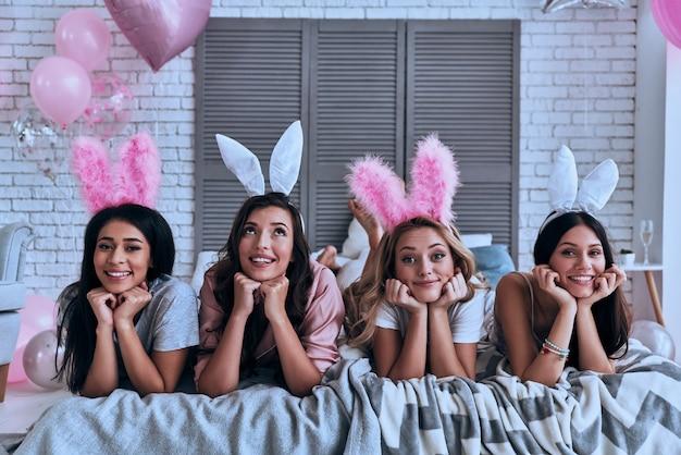 純粋な美しさ。ベッドに横になって笑っているバニーの耳に4人の魅力的な若い女性