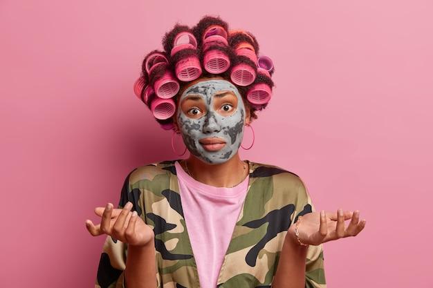 순수한 아름다움과 헤어 스타일링 개념. 머리카락 curlers와 얼굴 마스크를 가진 의심스러운 여자, 손바닥을 옆으로 펼치고, 어려운 질문에 대한 답을 모르고, 국내 옷을 입고, 분홍색에 고립 된