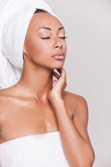 Чистая красота. красивая молодая афро-американская женщина, завернутая в полотенце, держа глаза закрытыми и касаясь ее лица, стоя на сером фоне
