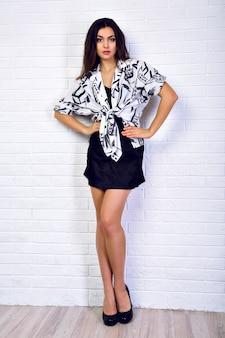 純粋な美しさ。黒のショートドレスで大きなかかとの上に立って、カメラを見て美しい若い女性