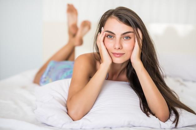 Чистая красота. красивая молодая женщина поправляет волосы и лежит на кровати у себя дома