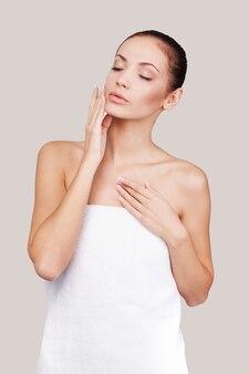 Чистая красота. красивая молодая женщина, завернутая в полотенце, держа глаза закрытыми и касаясь ее лица, стоя на сером фоне