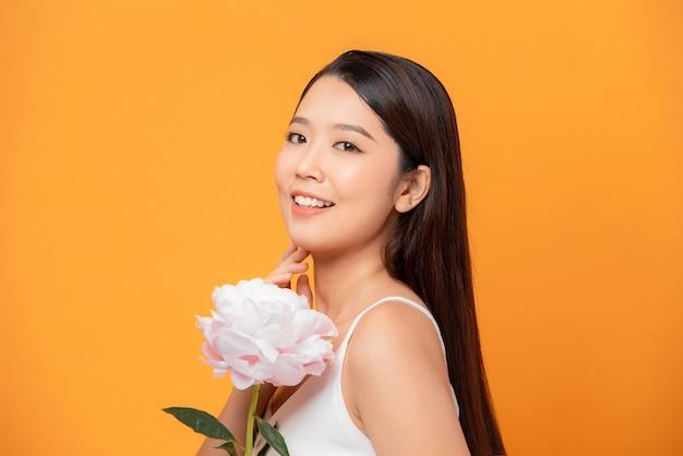 純粋な美しさ。ピンクの牡丹の花を持っている女の子