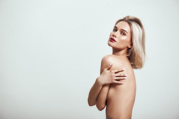 彼女の胸を覆うブロンドの髪を持つ魅力的なスリムな女性の純粋な美しさの側面図