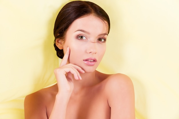 Pure clean beauty woman posing with yellow fabric on white