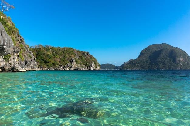 Чистые прозрачные бирюзовые воды филиппинского моря на фоне высоких скал.
