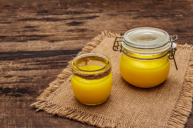 Pure or desi ghee (ghi), clarified melted butter. healthy fats bulletproof diet concept or paleo style plan. glass jar, silver spoon on vintage sackcloth.