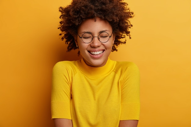 순수한 감정과 진지한 행복. 기쁜 십대 소녀는 웃고, 재미있는 것을보고 웃으며, 눈을 감고, 이빨 미소를 지으며, 멋진 멋진 소식에 감명을 받고, 노란색 옷을 입습니다.
