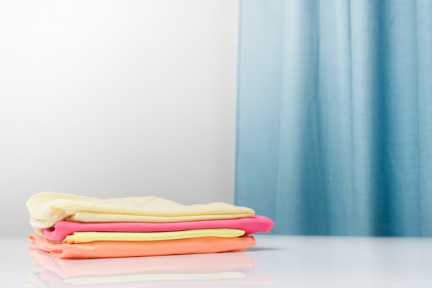 Pure fragrant laundry clothes of bright colors are stacked. freshness, cleanliness and housework concept.