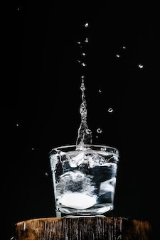 Pure fresh water in glass, an effervescent tablet with vitamin c falls into the glass, splashing over the water, dark wall with copy space for text, selective focus. close-up, vertical frame