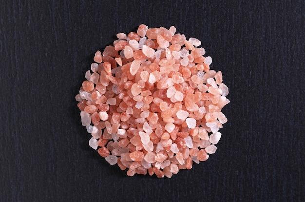 검은 돌 배경 상위 뷰에 순수한 손으로 만든 핑크 소금 거친 갈기