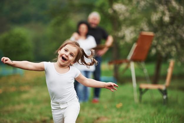 純粋な幸福。祖母と祖父は孫娘と屋外で楽しんでいます。絵画の構想