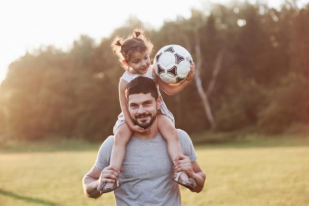 純粋な幸福。背景の美しい草や森で彼の娘とお父さんの写真。