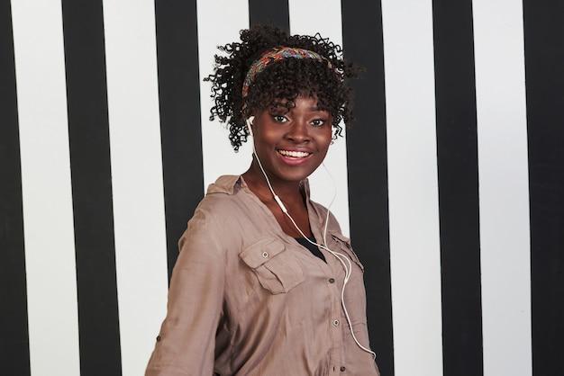 純粋な幸福。微笑んでいるアフロアメリカンガールは、背景に垂直の白と黒の線でスタジオに立っています。
