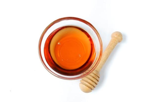 Стеклянная миска из чистого меда с деревянной ложкой меда, изолированные на белом фоне