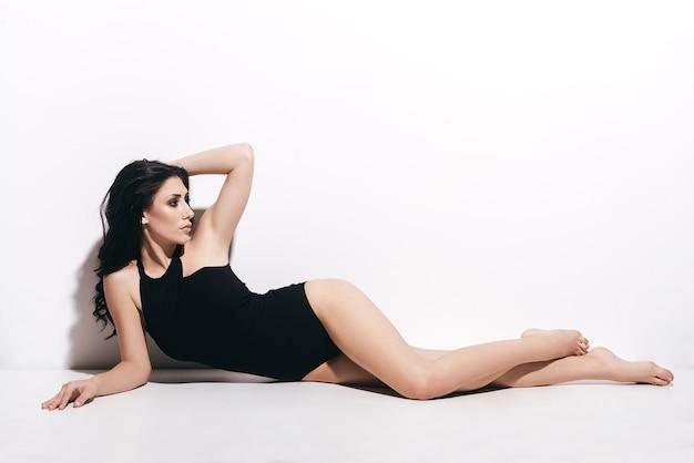순수한 완벽함. 검은 수영복을 입은 매력적인 젊은 여성이 머리카락에 손을 잡고 흰색 배경 앞에 누워 있는 동안 시선을 돌립니다.