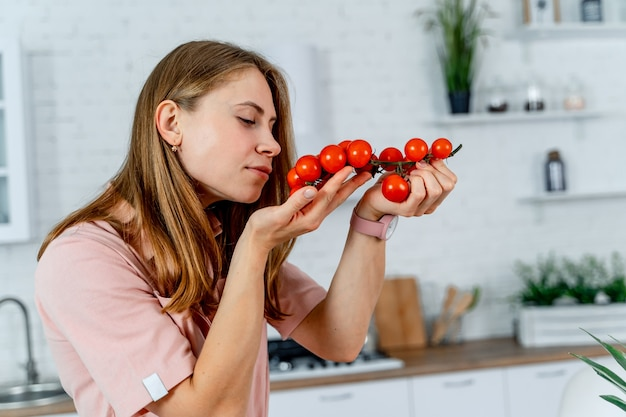 キッチンの背景の女性の手に純粋で熟したジューシーなトマト。野菜や果物がいっぱいのテーブル、モダンなキッチン