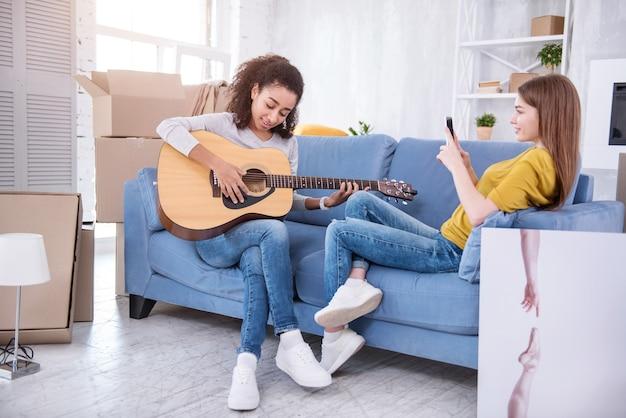 Чистый талант. очаровательная молодая девушка сидит на диване рядом со своим соседом по комнате и снимает, как она играет на гитаре