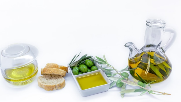 Pure virgin olive oil with olives, olive branch, olive tree and bread on a light surface