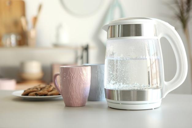 Чистая вода кипит в электрочайнике на столе на кухне
