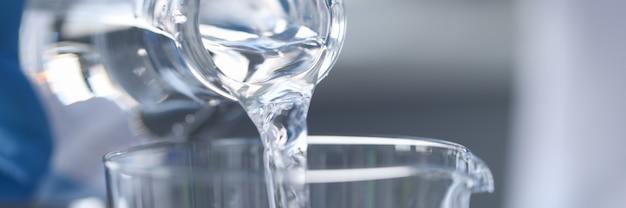 Чистая вода льется из стеклянной бутылки в стеклянную очистку воды через концепцию фильтра