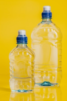 Pure water in plastic bottle on bright yellow