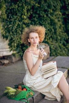 純水。手に水のボトルを持って階段に座っている若い女性