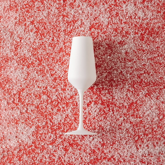 Pure white champagne glass over a festive red christmas background sprinkled with snow in square format for a holiday greeting card or invitation