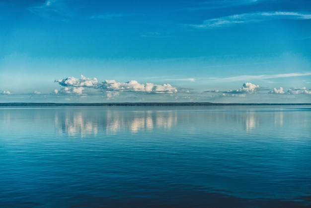 Pure white clouds of the sky reflected in the water of the sea