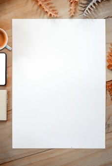 Pure white page with cup of coffee, smartphone and notebook on wooden table and dried leaves