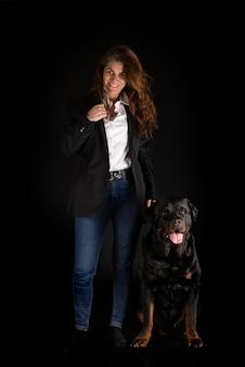 Чистокровный ротвейлер и женщина, изолированные на черном