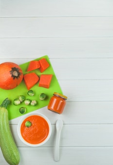 Puree from pumpkin in the plate and jar on wooden background