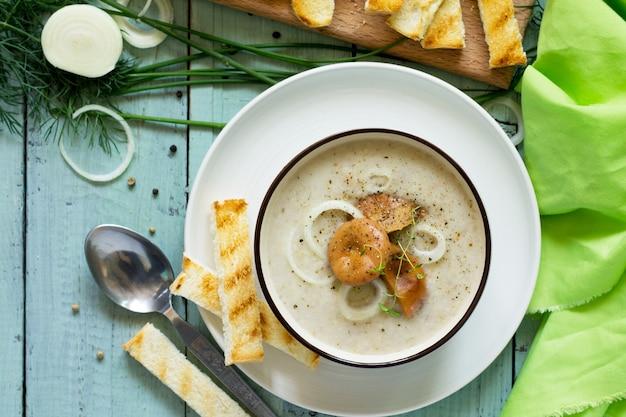 Суп-пюре из грибов с гренками в миске на кухонном деревянном столе