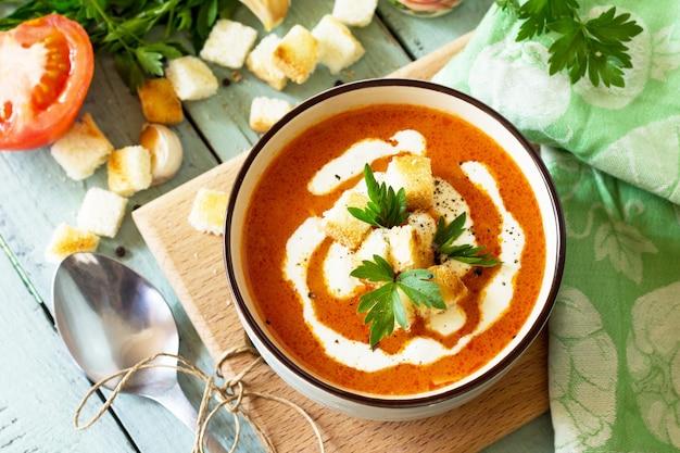 Суп-пюре из томатов с гренками и сливками в миске на кухонном деревянном столе