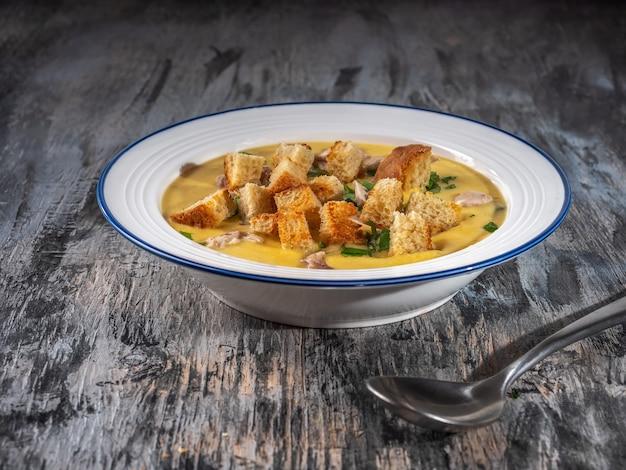 Суп-пюре с гренками и зеленью на курином бульоне в белой тарелке ложкой