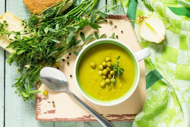 Суп-пюре с зеленым горошком в миске на кухонном деревянном столе